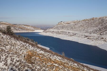 horsetooth rock: Horsetooth Reservoir in Colorado with highway and view of Fort Collins and plains over a dam, winter scenery with snow and still unfrozen water Stock Photo