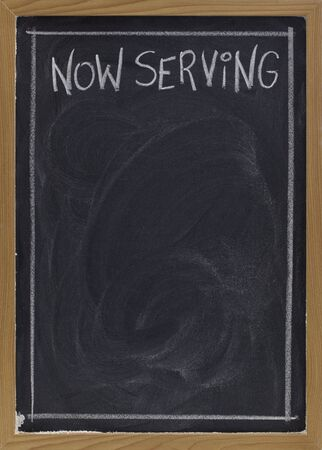 now serving - white chalk handwriting on blackboard with blank space below for a menu Stock Photo - 6134703