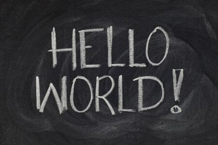 Hello, World! message from a first computer program used in many introductory tutorials for teaching programming language, white chalk handwriting on blackboard