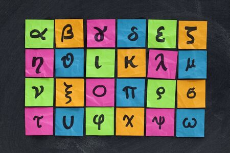 Greek alphabet (lower case) - handwriting on colorful sticky notes posted on blackboard with white chalk texture Stock Photo