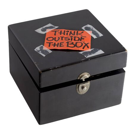 think outside the box - orange label (reminder note) casually taped on top of old black painted wooden box with dents and scratches, isolated on white with clipping path Stock Photo - 6149825