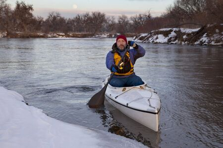 mature male paddling a decked expedition canoe on river in winter scenery (South Platte in eastern Colorado)