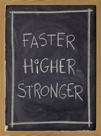 higher: (faster, higher, stronger) handwritten with white chalk on blackboard Stock Photo