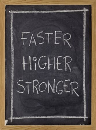 motto: (faster, higher, stronger) handwritten with white chalk on blackboard Stock Photo