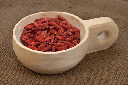dried Tibetan goji berries (wolfberries) on a rustic unfinished wooden scoop, burlap background Stock Photo - 6231755