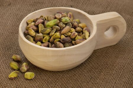 raw shelled pistachio nuts on a rustic, wooden scoop with brown burlap background Stock Photo - 6242169