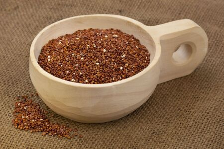 red quinoa grain on a rustic, wooden scoop against brown burlap background Stock Photo - 6242168
