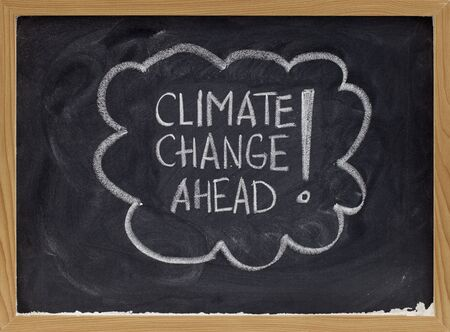 climate change ahead - white chalk handwriting on a school blackboard photo
