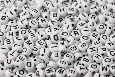 white plastic beads with black letters placed randomly