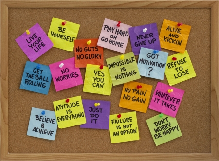 positivity: motivational slogans and phrases - colorful reminder notes with handwriting on cork bulletin board Stock Photo