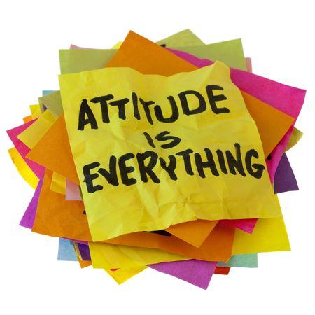 ACTITUD: lema motivacional en una pila de notas de recordatorio coloridos aislados en blanco