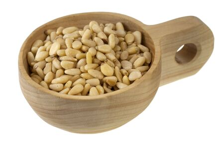 pine nuts on a rustic wooden bowl (scoop) isolated on white Stock Photo - 6330051