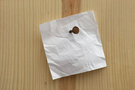 white crumpled blank reminder note nailed to a wooden plank or wall Stock Photo
