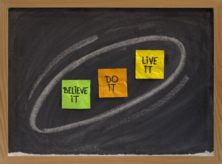 to believe: believe it, do it, live it - motivational concept on blackboard, color sticky notes and white chalk drawing Stock Photo