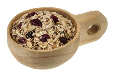 muesli cereal in (rolled oats with raisins, cranberries, slices almonds and flax seeds) on a rustic wooden scoop or bowl isolated on white Stock Photo - 6370885