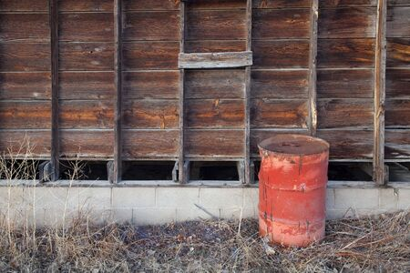 old rusty oil barrel and weathered wooden barn wall Stock Photo - 6370886