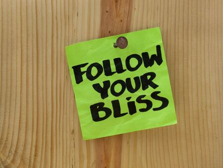 bliss: follow your bliss handwriting on a green sticky note nailed to wooden wall or plank Stock Photo