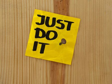 nailed: just do it, motivational reminder handwritten on yellow sticky note and nailed to wooden wall or plank