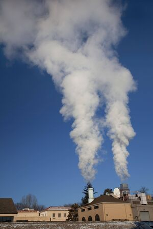 two smoke and steam plumes from a small heating plant on cold winter mornings at Colorado State University campus, Fort Collins Stock Photo - 6423833