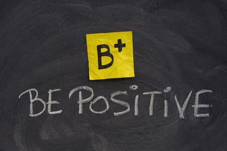 B+, be positive concept, yellow sticky note and white chalk handwriting on blackboard