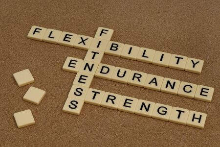 endurance, flexibility, strength - fitness training goals concept, crossword with ivory letter blocks on cork bulleting board Stock Photo - 6514231