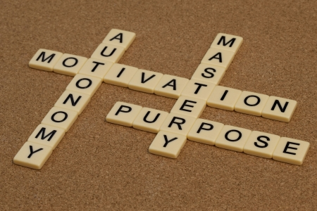 three elements of true motivation - mastery, autonomy, purpose - crossword with ivory letter blocks on cork board