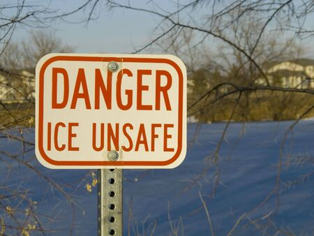 unsafe: danger ice unsafe warning sign with a frozen pond in background Stock Photo