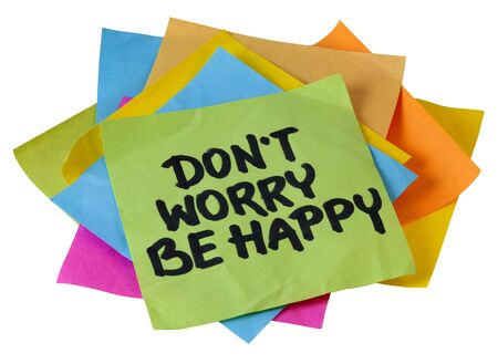 positivity: dont worry be happy phrase, a quote from Meher Baba, an Indian mystic and spiritual master (before it was used in a song lyrics), handwriting on a pile of sticky notes isolated on white