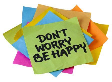 ansiedad: no te preocupes ser feliz de la frase, una cita de Meher Baba, un maestro espiritual y m�stico indio (antes de que se us� en una letra de la canci�n), escritura a mano en un mont�n de notas adhesivas aislados en blanco Foto de archivo