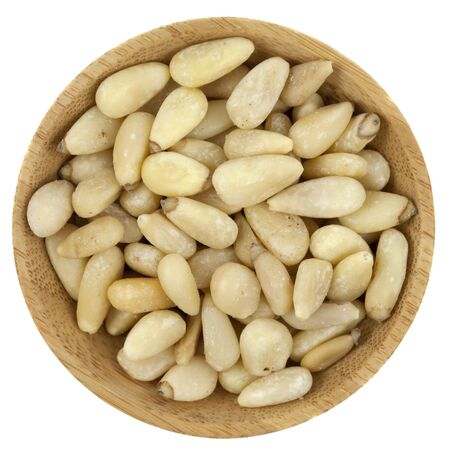 pine nuts on a small round wooden bowl isolated on white Stock Photo - 6659808