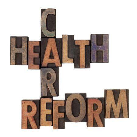 crossword van de hervorming van de gezondheidszorg in oldtimers houten letterpress typen in inkt, geïsoleerd op wit gekleurd
