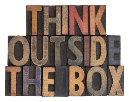think outside the box phrase in vintage wooden letterpress type, stained by ink, isolated on white  photo