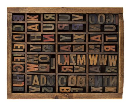 scratched: vintage wood letterpress types, stained by ink, placed randomly in typesetter drawer, isolated on white Stock Photo