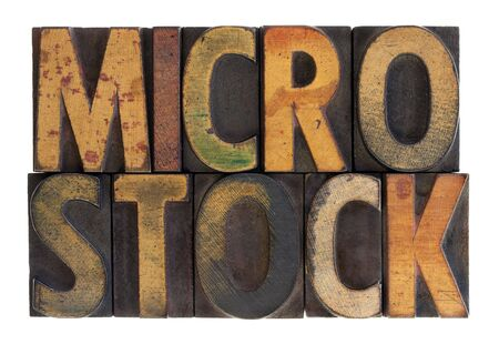 microstock: the word microstock in vintage wood block type, stained by color ink, isolated on white