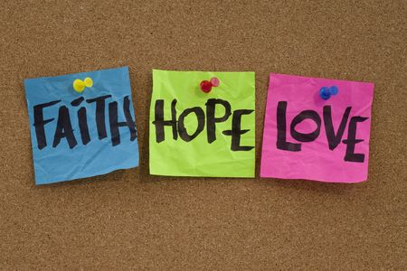 christian faith: spiritual reminder or methaphysical concept - faith, hope and love handwritten on colorful notes and posted on cork bulletin board Stock Photo