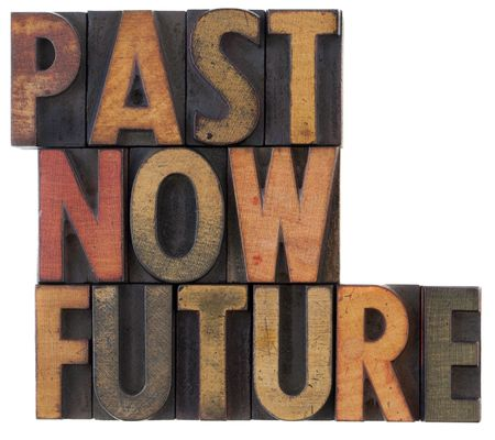 past, now, future words in vintage wooden letterpress block types, stained in color ink, isolated on white photo