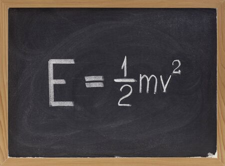 classical mechanics: kinetic energy equation of classical Newtonian mechanics connecting it to mass and velocity of a point object  - white chalk handwriting on blackboard