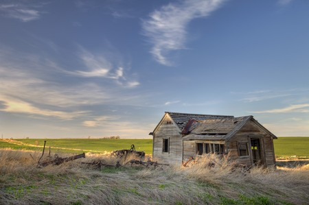 old abandoned house and farming machinery on Colorado prairie with green fields in background Stock Photo - 6881274