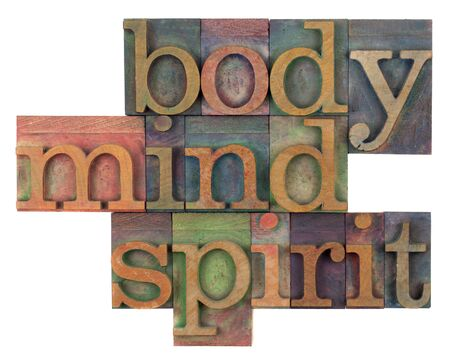 letterpress words: body, mind and spirit in vintage wooden letterpress types, stained by ink in different colors, isolated on white
