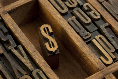 monetary concept: financial or monetary concept,  dollar symbol - vintage letterpress wooden type (condensed gothic) in old printer drawer among other letters stained by dark ink