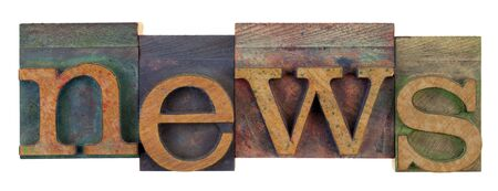 the word news in vintage wooden letterpress type, lower case, stained by colorful inks, isolated on white photo