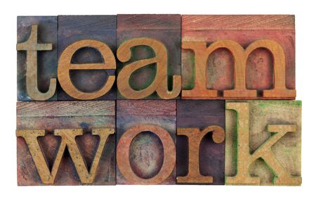 the word teamwork in vintage wooden letterpress type, stained by colorful inks, isolated on white Stock Photo