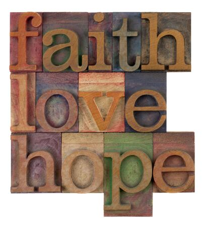 biblical, spiritual  or metaphysical reminder - faith, hope and love in old wooden letterpress type blocks, stained by colorful inks, isolated on white photo