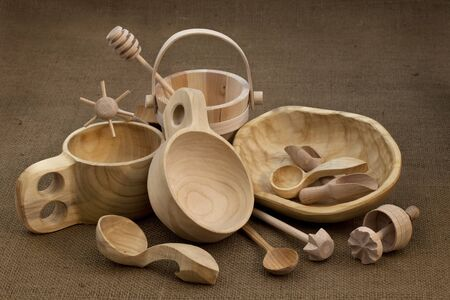 Polish folk wood craft (cups, bowl, spoons, scoops, bucket, kitchen utensils, butter mold, honey drizzler) on burlap background Stock Photo - 6983876