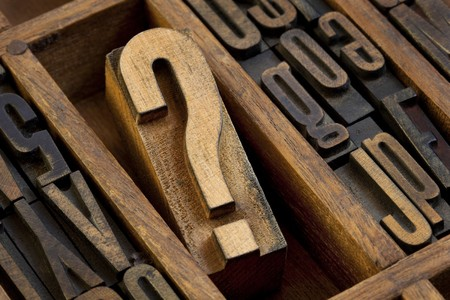 letterpress letters: question mark - vintage wooden letterpress type block in old typesetter drawer among other letters stained by ink