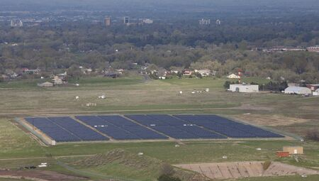 large solar energy farm (3.3MW) at foothills campus of Colorado State University, aerial view from a mountain ridge with a hazy view of Fort Collins city in background photo