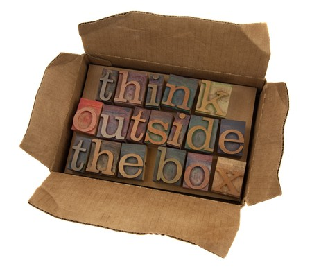 letterpress words: think outside the box concept, words  in vintage letterpress type  in open cardboard box, isolated on white