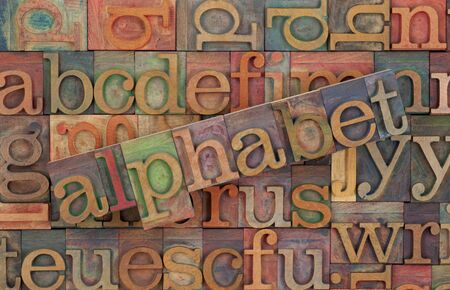 the word of alphabet across a background of vintage wooden letterpress type blocks, stained by color inks Stock Photo - 6983901