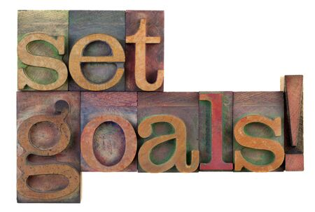 setting goals: Set goals reminder in vintage wooden letterpress type blocks, stained by color ink, isolated on white Stock Photo