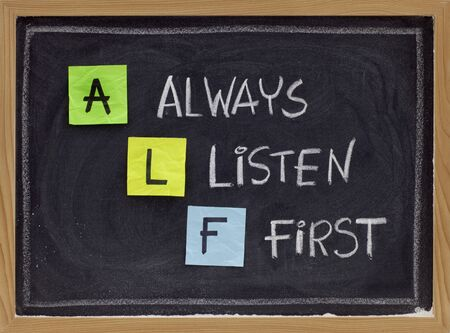 selling service: ALF acronym (always listen first) - good advice for training, counselling, customer service, selling or relationships, sticky notes and white chalk handwriting on blackboard Stock Photo